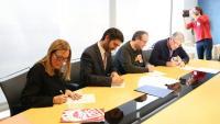 El conseller Jordi Puigneró i els representants dels sindicats, signant aquest dimarts l'acord que ha permès desconvocar la vaga