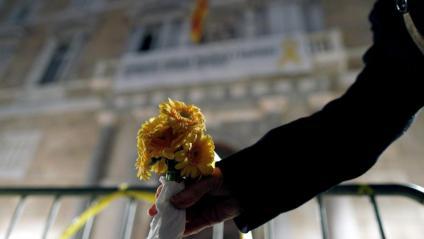 Una dona col·loca un ram de flors grogues en una tanca situada davant el Palau de la Generalitat, on aquest dijous encara hi havia una pancarta de suport als presos polítics i un llaç groc