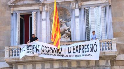 Dos membres de l'equip de Torra pengen la nova pancarta al balcó de la Generalitat, aquest divendres a la tarda