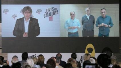 El cap de llista de JxCat a les europees, Carles Puigdemont, intervenint per pantalla al costat de Jordi Turull, Joaquim Forn i Josep Rull al míting central de la formació, aquest diumenge a Sant Cugat del Vallès