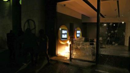 Una oficina de la Caixa amb flames i els vidres trencats