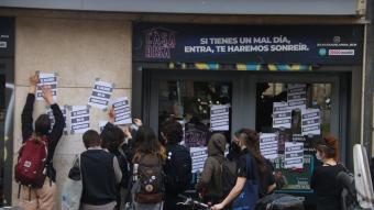 Un grup de manifestants enganxa cartells davant la façana del Teatre Borràs, durant la vaga d'estudiants d'arts en viu aquest dilluns a Barcelona