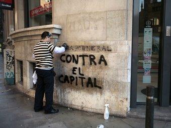 Un operari neteja una pintada l'endemà de la vaga general.  Foto:JOSEP LOSADA
