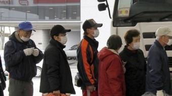 Ciutadans japonesos fan cua ordenadament en una gasolinera per omplir bidons de querosè després del terratrèmol.  AFP