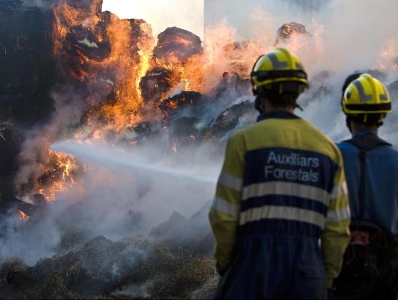 Un parell de bombers observen les flames del foc que va cremar ahir en una finca de Serra de Daró LLUÍS SERRAT