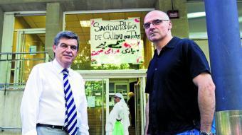 Joan B. Casas, degà del Col·legi d'Economistes de Catalunya i José García Montalvo, catedràtic de l'UPF davant un CAP del Raval amb un cartell en contra de les retallades.  Foto:JOSEP LOSADA