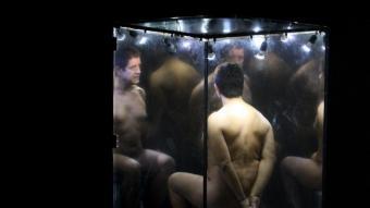 Pedro Casablanc, dins l'urna de vidre, i el seu rostre, projectat, en un moment de la representació. LLUÍS SERRAT