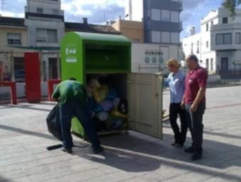 Operaris municipals recullen la roba dipositada als contenidors. EL PUNT AVUI