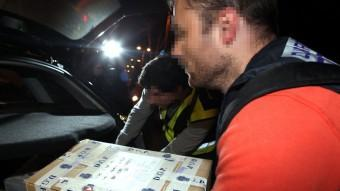 Agents de la policia espanyola carreguen caixes al cotxe després de l'escorcoll de la seu de l'agència de detectius Método 3 a Barcelona ACN