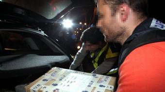 Dos agents de la Policía Nacional amb unes caixes de material comissat abans-d'ahir a l'agència Método 3 ACN/ ORIOL CAMPUZANO
