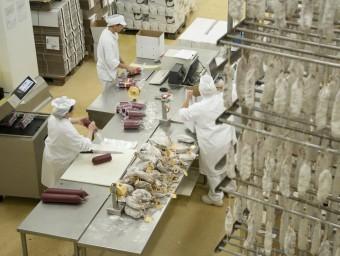 Tres treballadors de Caula envasant i etiquetant diferents embotits.  Foto:CAULA