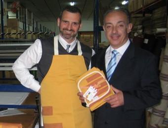 Miquel Bordes i Antoni Canellas mostren el davantal i la presentació del lot de productes Cata-lands que fabriquen.  Foto:A. AGUILAR