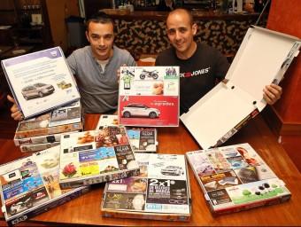 Josep Maria Pardo i Lucas Márquez mostren les caixes a la pizzeria La Pèrgola, de Vilafranca del Penedès.  JUANMA RAMOS