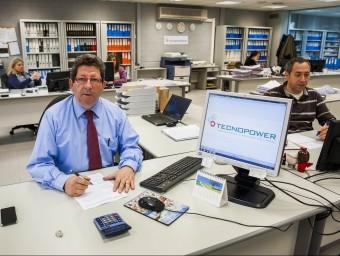 Vicent Sospedra, a la taula que utilitza a l'oficina comuna, amb alguns dels treballadors.  Foto:JOSEP LOSADA