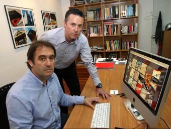 Joan Ureña -assegut- i Jesús Cuesta, mostren alguns dels dissenys que han elaborat durant aquests anys.  LLUÍS SERRAT