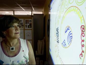 La directora del gabinet de grafologia +grafo, Ana López, observa un dels exercicis que fan els alumnes.  J. C. LEÓN