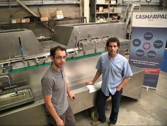 Albert Martínez, a la dreta de la imatge, davant d'una de les màquines del grup.  MANEL LLADÓ