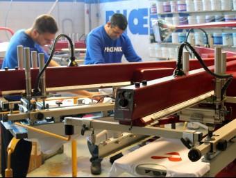Dos operaris estampant samarretes a la fàbrica de l'empresa, situada a Argentona.  CAMISETAS.INFO
