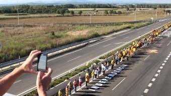 Uns ciclistes fotografien la Via Catalana al seu pas per uns dels pocs trams desdoblats de l'N-II a Girona, LLUÍS SERRAT ANDREU PUIG / JOSÉ CARLOS LEÓN