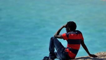 Un jove africà mirant el mar després d'arribar a l'Estat. AFP