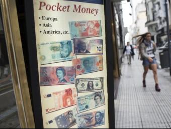 Una dona passa davant d'una casa de canvi de moneda de Buenos Aires.  AFP