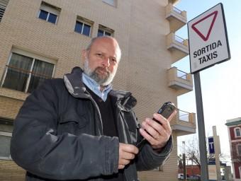 José Franco amb el seu telèfon intel·ligent en una parada de taxis davant l'estació de trens de Mataró.  QUIM PUIG