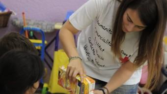 Una voluntària de la Creu Roja serveix el berenar a una nena JUANMA RAMOS