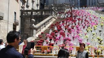 Uns turistes fotografiant ahir el projecte floral de l'escalinata de la Catedral LLUÍS SERRAT