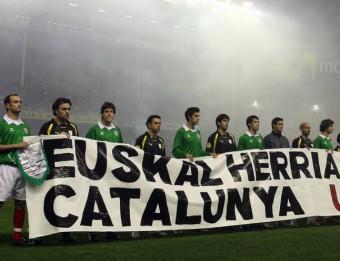 Els jugadors d'Euskadi i Catalunya , amb una pancarta reivindicant l'oficialitat de les seleccions, en el partit disputat a San Mamés l'any 2007 ORIOL DURAN