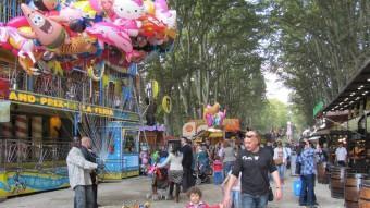 Un venedor de globus acoloreix l'entrada de la atraccions de la Devesa mentre les famílies passegen durant la diada de Sant Narcís D.V