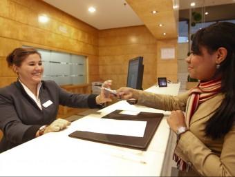 Recepcionista d'un hotel atén una clienta.  Foto:ARXIU/MARTA PÉREZ