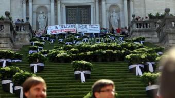Quim Masferrer i Carles Puigdemont, amb la pancarta dels activistes al fons. QUIM PUIG