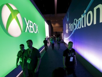 Attendees walk between Microsoft and Sony logos at E3 in Los Angeles.  REUTERS/LUCY NICHOLSON