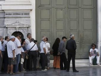 Ciutadans grecs fan cua davant una sucursal del Banc Nacional de Grècia en el centre d'Atenes EFE
