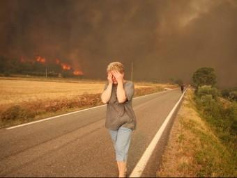 Una dona fugint de les flames que estaven cremant la seva granja el primer dia de l'incendi. LL. SERRAT