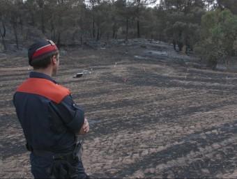 Un mosso d'esquadra observant la zona es va originar el foc, marcada pels investigadors ACN