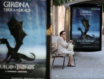 Una senyora asseguda en un banc entre anuncis de la sèrie que omplen Girona MANEL LLADÓ