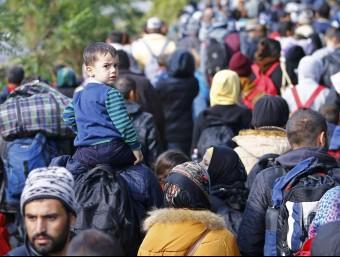 Un nen mira enrere enmig de la llarga cua de refugiats que caminen a Hongria per travessar la frontera amb Àustria REUTERS