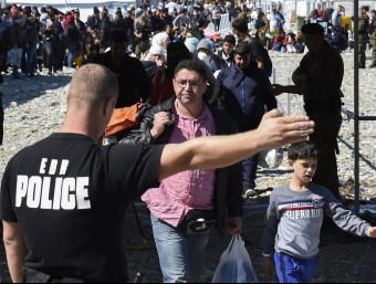 Un grup de refugiats siris reben instruccions d'un policia a la frontera amb Sèrbia.  ARXIU