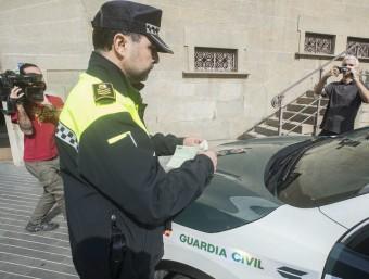 El cap de la Policia Local posa una multa a un dels cotxes de la Guàrdia Civil estacionat davant el consistori, aquest dimecres a Olot EFE