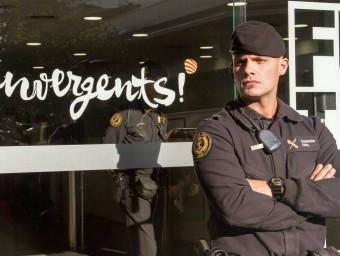 Un agent de la Guàrdia Civil en l'escorcoll a la seu de Convergència ALBERT SALAMÉ