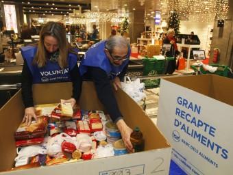 Dos voluntaris classifiquen els aliments en un dels punts de recollida oriol duran