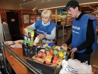 Alguns voluntaris en un supermercat de Llagostera, adherit a la campanya de recollida d'aliments. JOAN SABATER