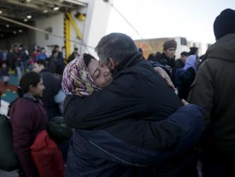 Una parella de refugiats s'abraça aquest divendres al desembarcar al port del Pireu, a prop d'Atenes, procedents de l'illa de Lesbos REUTERS