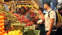Un grup de tres turistes observa els productes exposats en una parada de verdures de la Boqueria