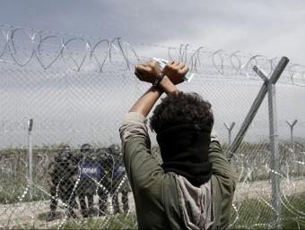 Un refugiat fa un als agents de policia macedònia que vigilen la frontera durant una protesta per reclamar-ne la reobertura, ahir a prop del camp d'Idomeni EFE