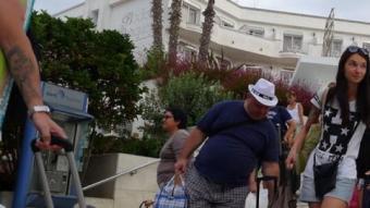 Turistes marxant d'un dels hotels que va haver de ser clausurats N.F