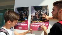 Dos estudiants enganxant un cartell a la universitat de Tarragona
