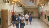 Un grup de visitants en una de les antigues galeries de l'antiga presó Model de Barcelona