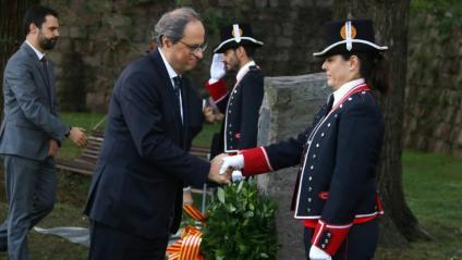 El president Quim Torra i el president del Parlament, Roger Torrent saluden dos oficials al final de l'ofrena davant el monument a Lluís Companys al Fossar de Santa Eulàlia del Castell de Montjuïc